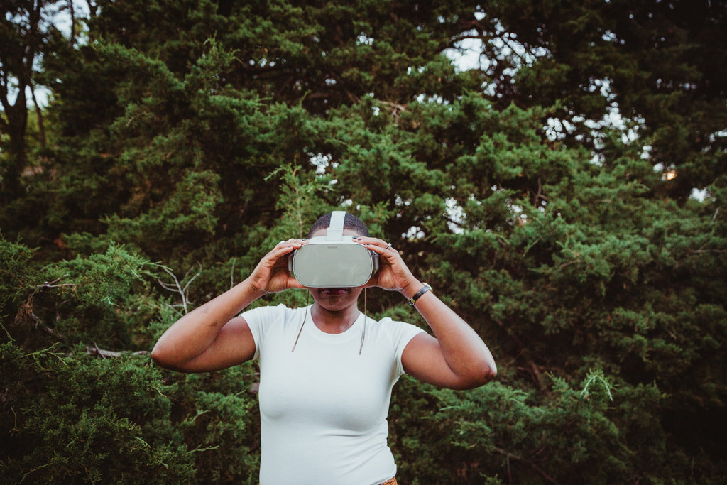 Chrystal wears her virtual reality headset while standing in front of green bushes and trees