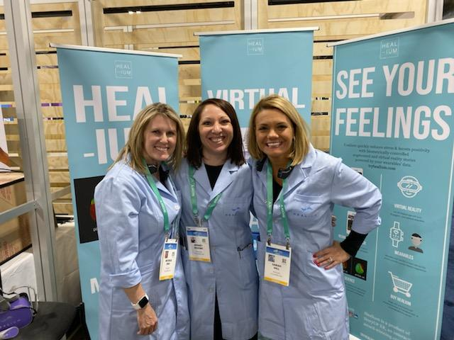 Wendy stands in the middle of Sarah and Michele at the CES conference. There are three pull up banner stands behind them.