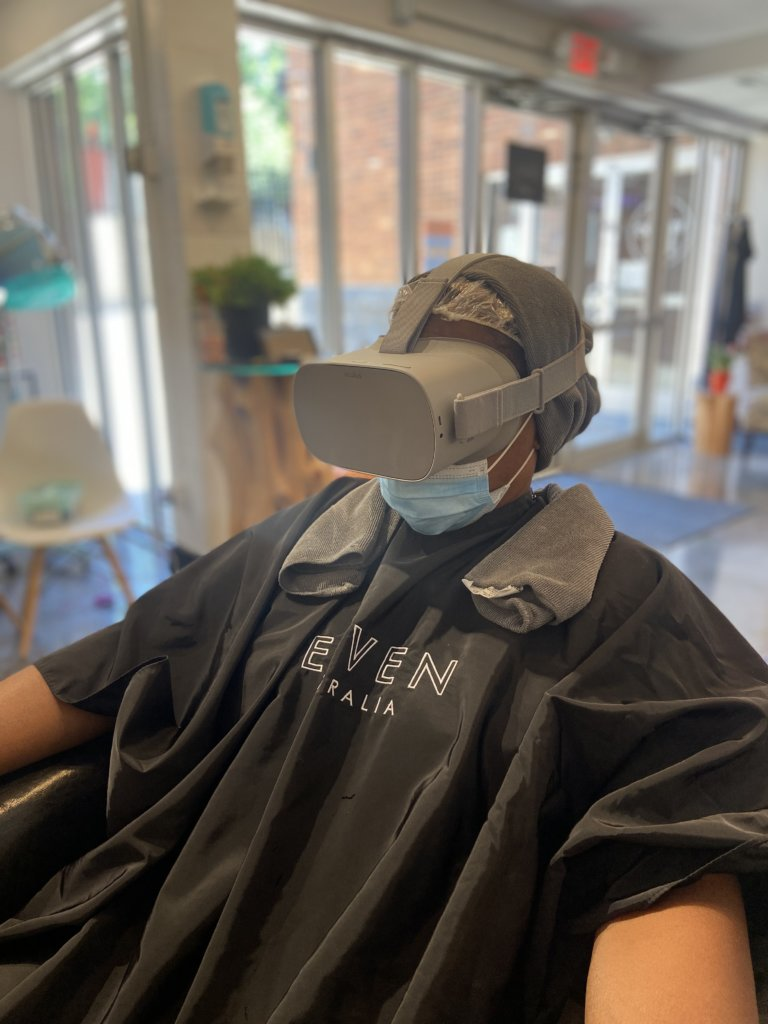 A woman sits in the salon chair getting a deep conditioning treatment while wearing a virtual reality headset