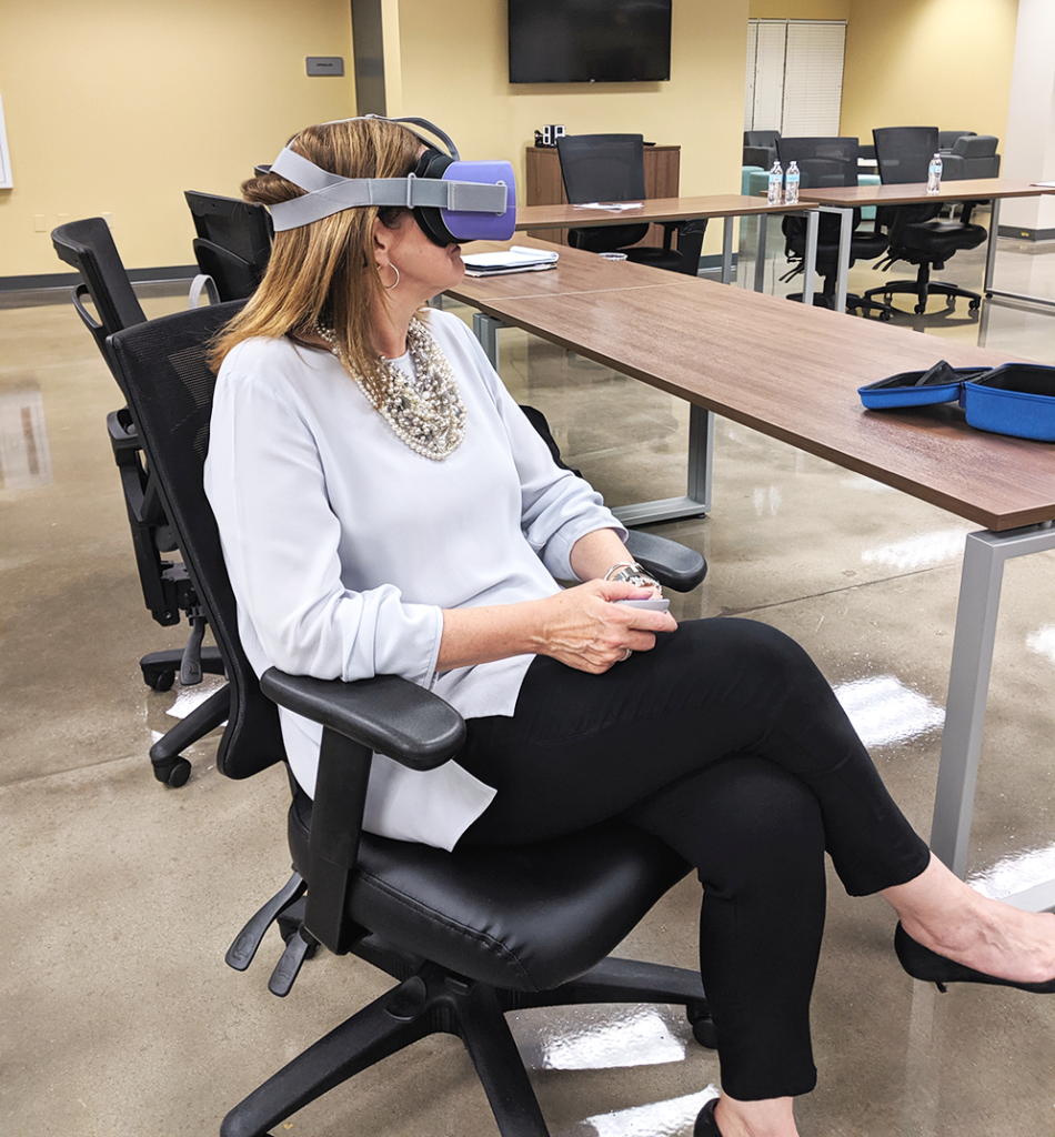 Woman sits relaxed in an office chair while using an Oculus Go headset