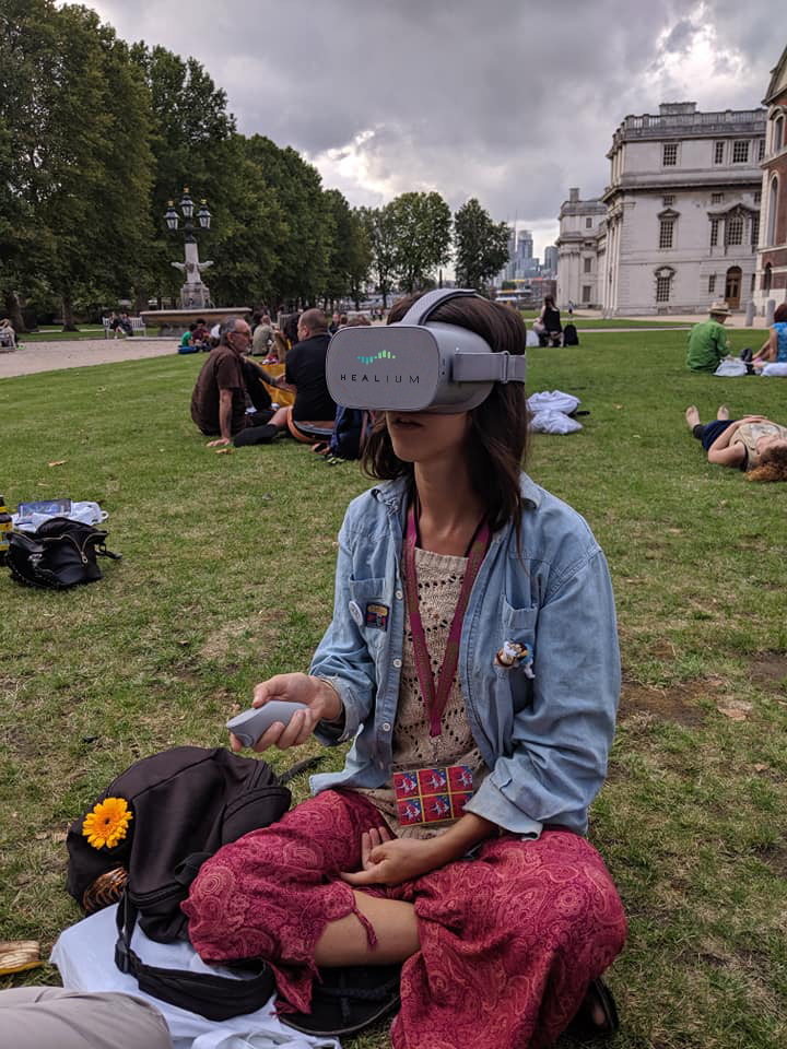 A student sits cross-legged while wearing an Oculus Go headset