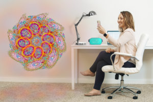 Wendy sits at her desk with computer, lamp, and Oculus Go headset. She uses her phone to view a colorful flower figure