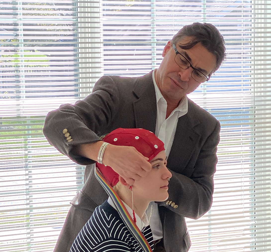 Jeff and Annarose demonstrate how an EEG cap is worn on the head